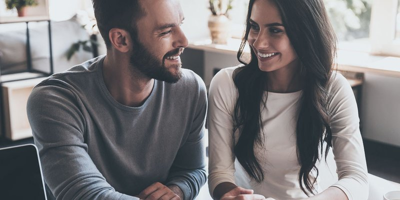 A young couple smile and look toward each other