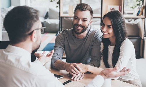 A young couple hold hands and listen to a mortgage broker