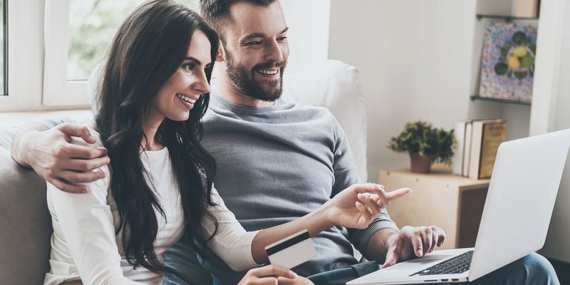 A man and a woman sit together with a laptop and a credit card