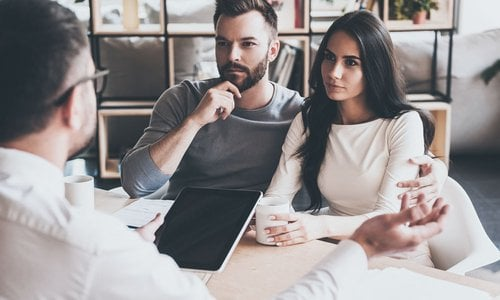 A young couple listen to a mortgage broker about their options