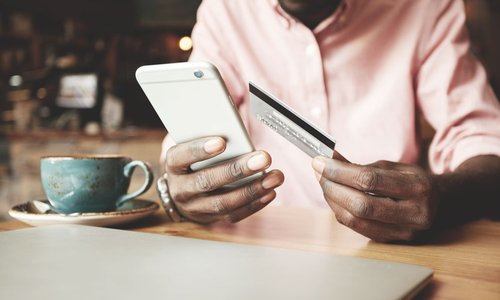 A close-up of a man holding his credit card and typing into his smartphone