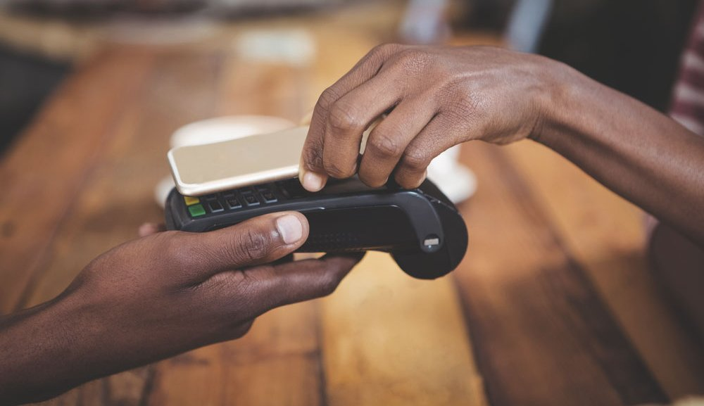 A customer uses their smartphone to pay with their mobile wallet