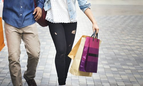 Two people walk down the street with shopping bags