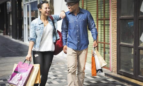 A man and a woman walk down the street with shopping bags