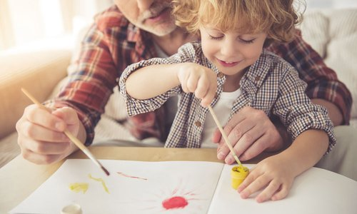 An older man helping a young child paint a picture