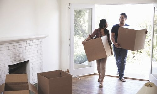 A young couple moving boxes into their new home