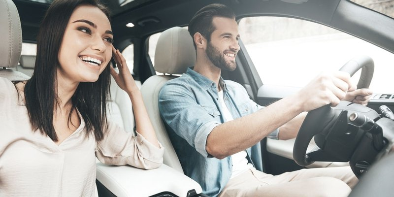 A male driver sits smiling with a female passenger on a bright day