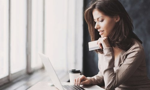A woman sits in front of her computer with her credit card in one hand and a coffee on the table