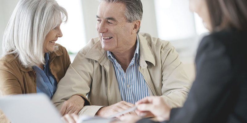 An older couple look very happy as they are shown documents