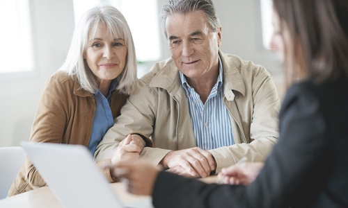 An older couple sit with a financial advisor