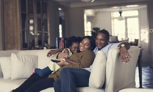 A family sitting on the couch about to watch TV