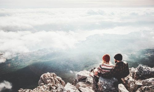 A young couple sit at the edge of a mountain top