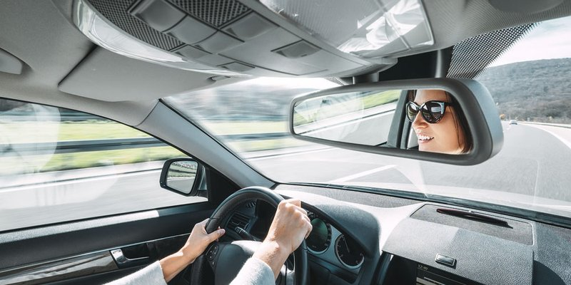 A woman is seen smiling in the rear-view mirror as she drives down a highway