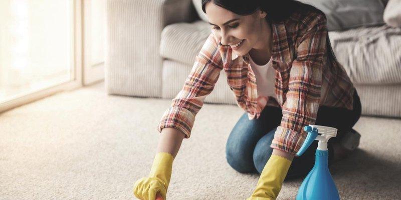 A woman scrubbing her carpet