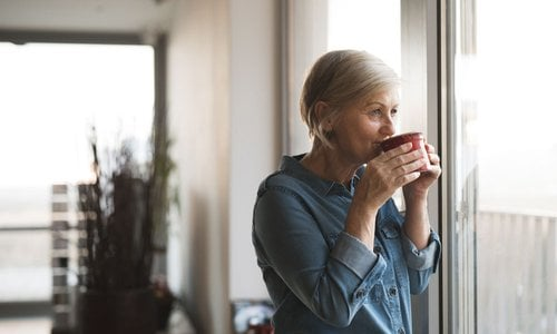 An older woman sips her coffee while staring out the window of her home