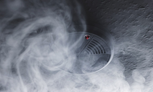 Smoke swirls around an inactive smoke detector