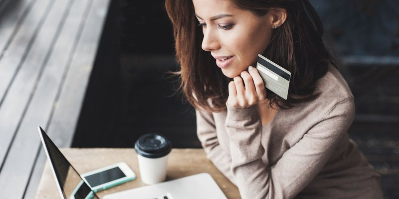 A woman sits at a table and rests her hand and a credit card against her chin