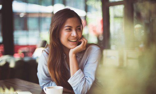 A young woman smiles while sitting on a patio with her laptop and a latte
