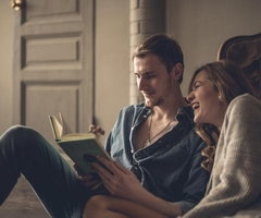 A young couple reading a book together