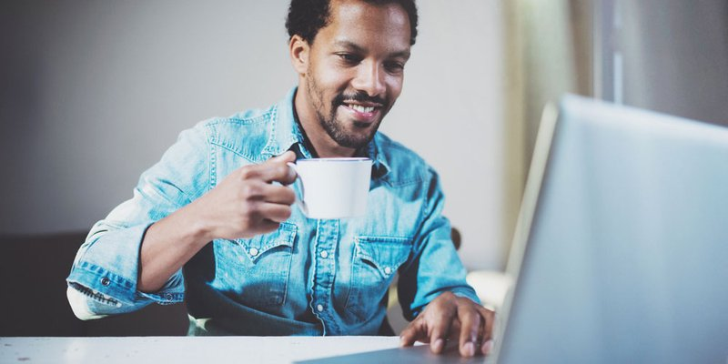 A man sits drinking a coffee while scrolling through his computer