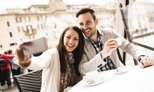 A young couple take a selfie at a cafe abroad