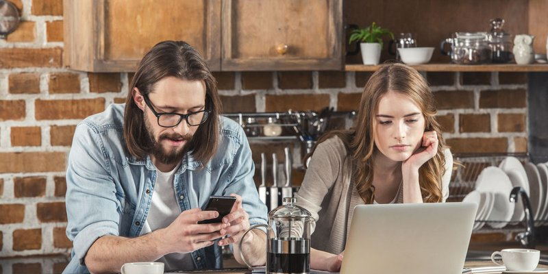 A man sits using his smartphone next to a woman using her laptop