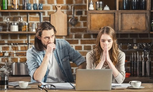 A man and woman look overwhelmed as they calculate their expenses