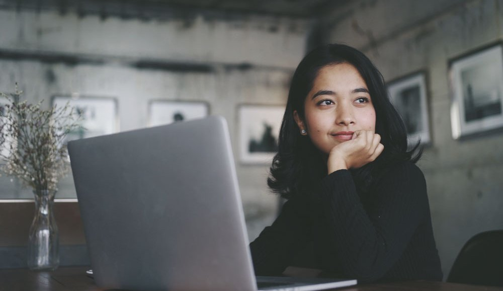 Young woman sits in front of a computer and softly smiles while looking off into the distance.