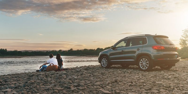 A couple sits on the edge of a riverbank a short distance away from their vehicle