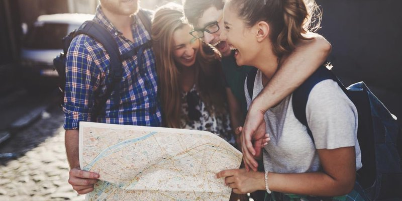 A group of young people laugh and look at a large map