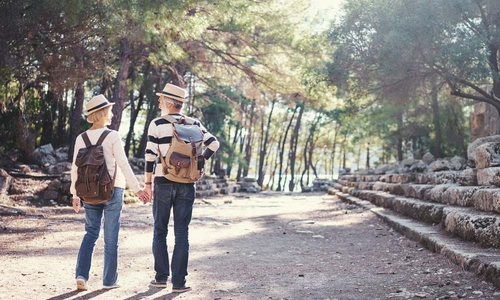 An older couple exploring ruins on their trip