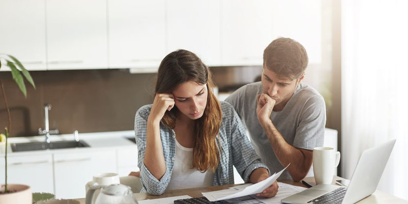 A young couple look overwhelmed calculating their bills