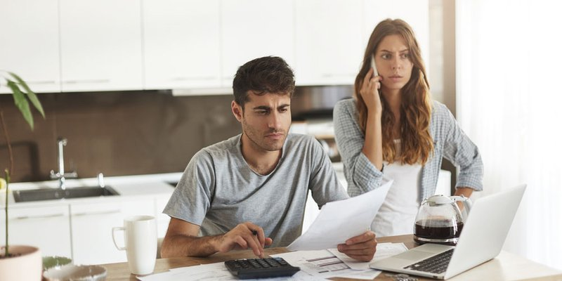 A woman looks upset while she speaks on the phone next to a man calculating bills
