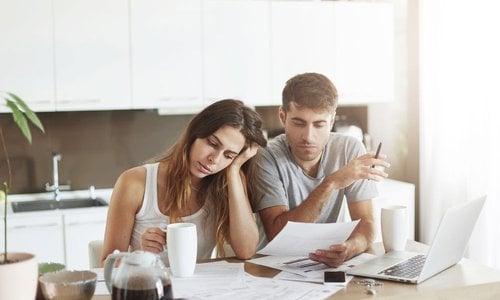 A couple look frustrated at their many bills