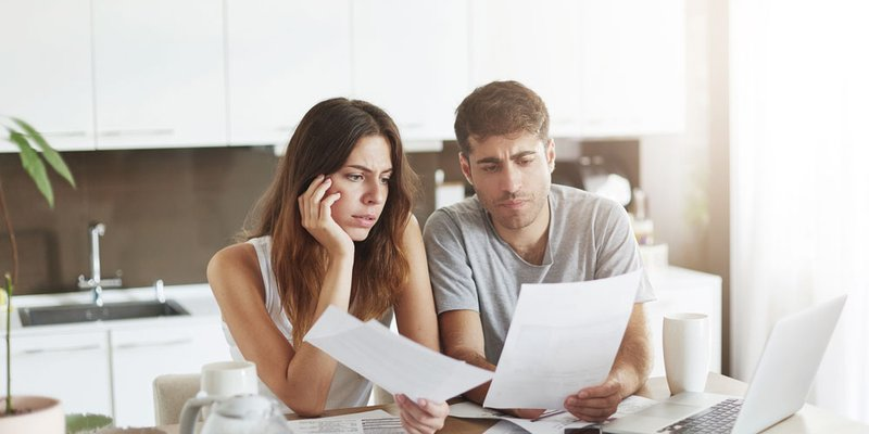 A man and woman look worried as they scan their statements