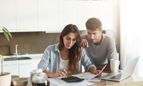 A man looks over a woman's shoulder as she calculates the monthly expenses