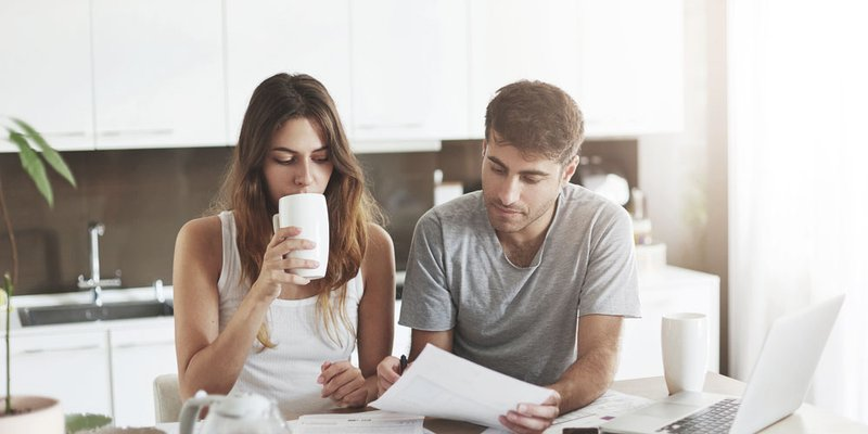 A woman sips her coffee as a man points to a document