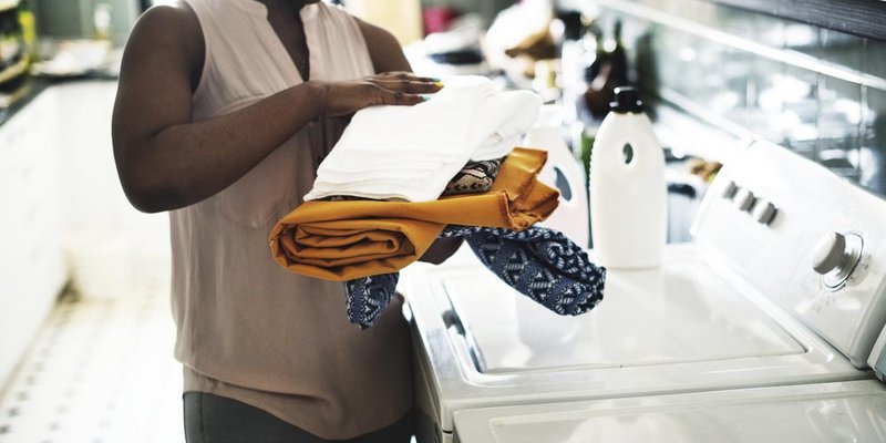 A close-up view of a woman folding laundry