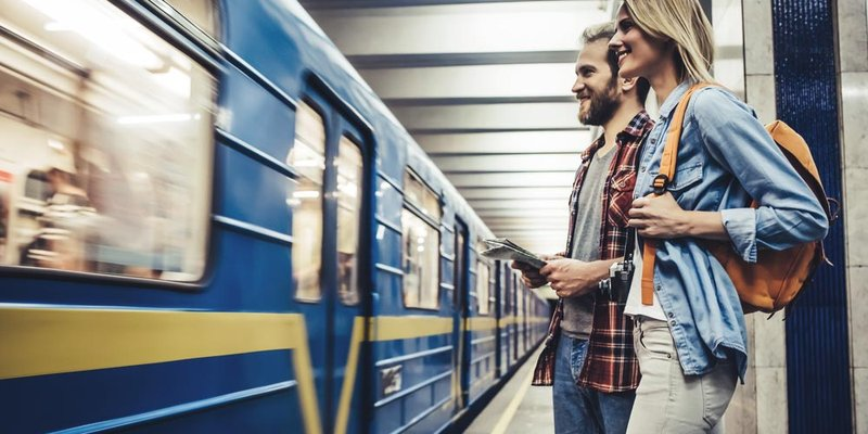 A young couple wait to board a train