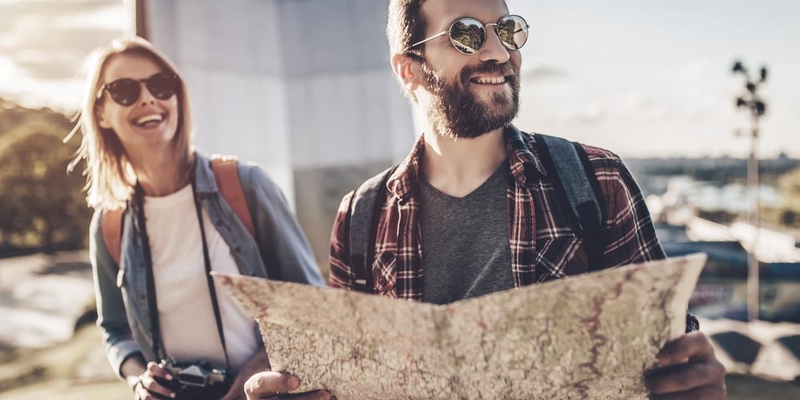 A man and woman look at a map and smile