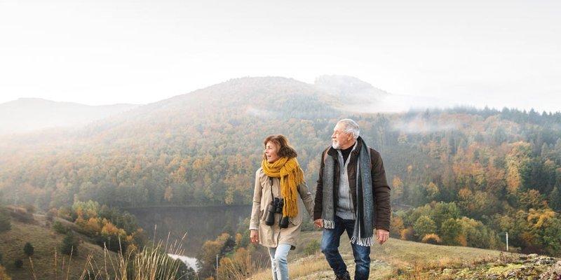 A senior couple walk up a foggy hillside