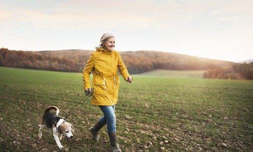 A woman in a yellow jacket jogs alongside her dog