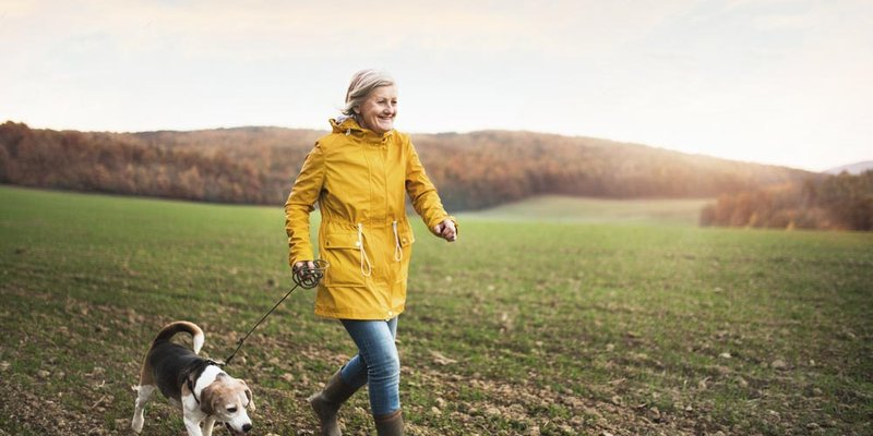 A woman in a yellow jacket jogs alongside her dog