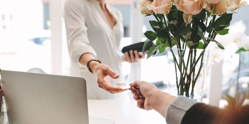 A woman hands her credit card to the employee at a flower shop