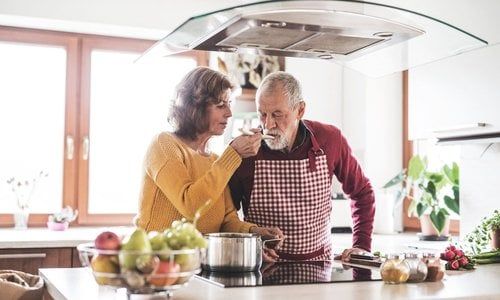 An older woman lets a man taste sauce off a wooden spoon in the kitchen