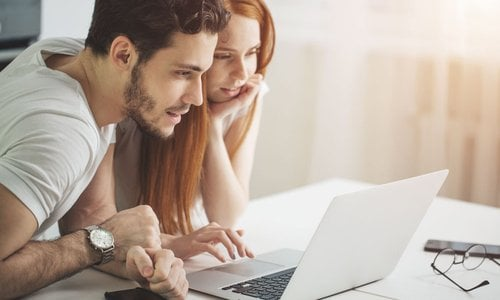 A young man and woman sit closely together at a table and look at something on a laptop