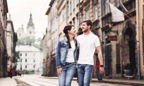A young couple walk down the street on their vacation