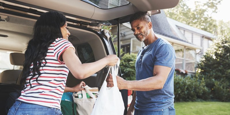 Two people taking the groceries in from the car