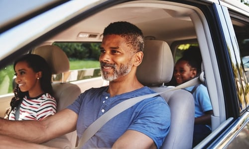 A family smiles while seated in a crossover vehicle