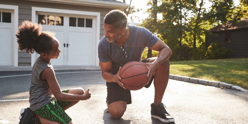 A father teaching his daughter how to play basketball